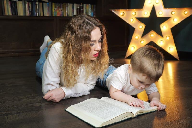 Portr?t der jungen Frau liest ein Buch mit ihrem kleinen Sohn lizenzfreie stockbilder