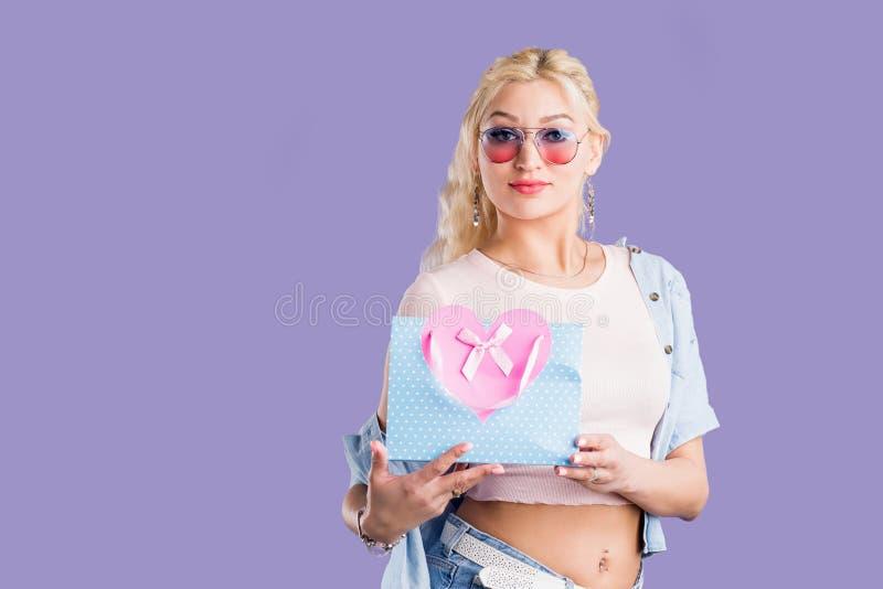 Portr?t der jungen gl?cklichen Frau mit der Einkaufstasche lokalisiert ?ber violettem Hintergrund stockfoto