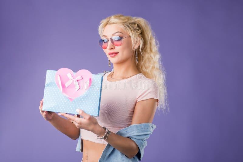 Portr?t der jungen gl?cklichen l?chelnden Frau mit der Einkaufstasche lokalisiert ?ber violettem Hintergrund lizenzfreie stockfotografie