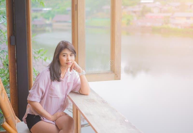 Portr?t der sch?nen asiatischen Frau Sitzen auf Holzstuhl Tabelle nahe dem Fenster stockfoto
