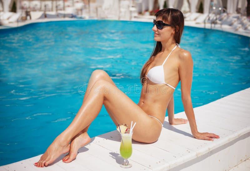 Portr?t der sch?nen gebr?unten exotischen Frau, die nahe Swimmingpool in der wei?en Badebekleidung mit gelbem Cocktail sich entsp lizenzfreies stockbild