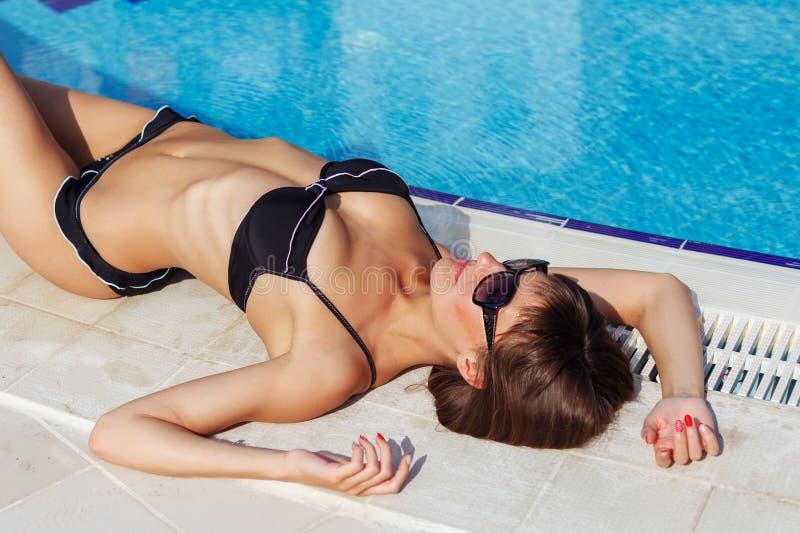 Portr?t der sch?nen gebr?unten Frau, die im Swimmingpool in der schwarzen Badebekleidung sich entspannt Kreative Gelpoliturmanik? lizenzfreies stockbild