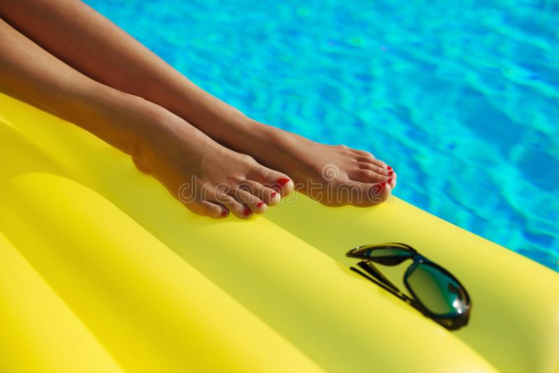 Portr?t der sch?nen gebr?unten Frau, die im Swimmingpool sich entspannt Sonnenbrille und aufblasbare matress Beine schlie?en oben lizenzfreie stockfotografie