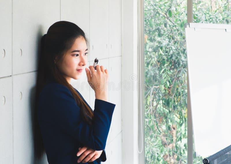 Portr?t der sch?nen Gesch?ftsfrau des asiatischen jungen langen Haares in der Marineblauklage denkend im modernen B?ro Zukunftspl stockfoto