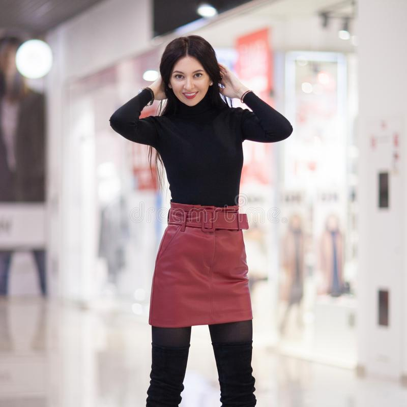 Portr?t der sch?nen gl?cklichen stilvollen Frau im roten Rock und in den modischen Schuhen, gehend in StadtEinkaufszentrum Modefr stockfotografie