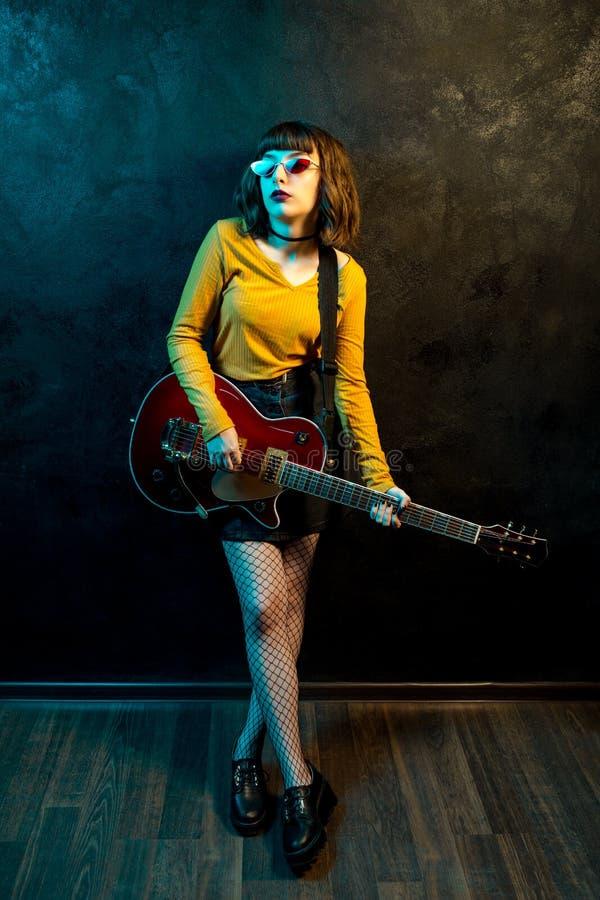 Portr?t der sch?nen jungen Hippie-Frau mit dem gelockten Haar mit roter Gitarre in den Neonlichtern Rockmusiker spielt lizenzfreies stockfoto