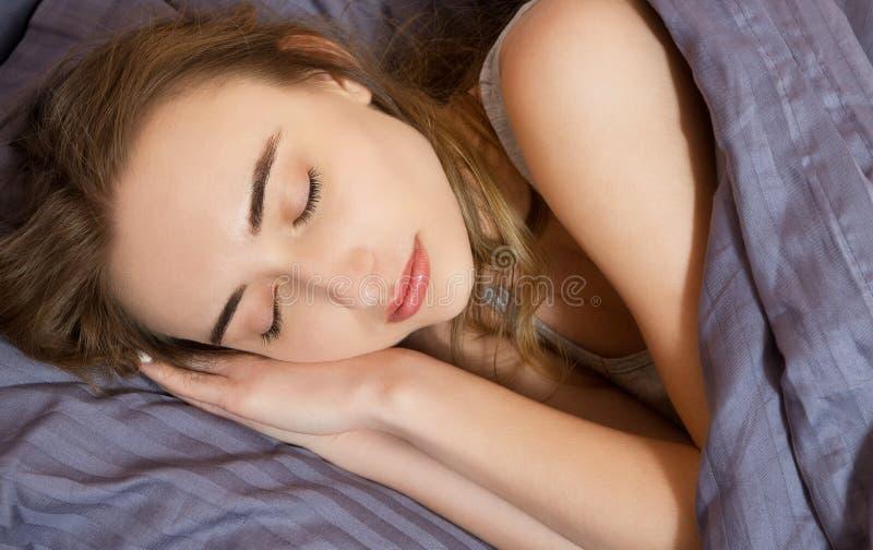 Portr?t der sch?nen jungen schlafenden Frau beim im Bett bequem und himmlisch liegen - Sonnenglanz vom Fenster auf ihrem Gesicht stockfoto