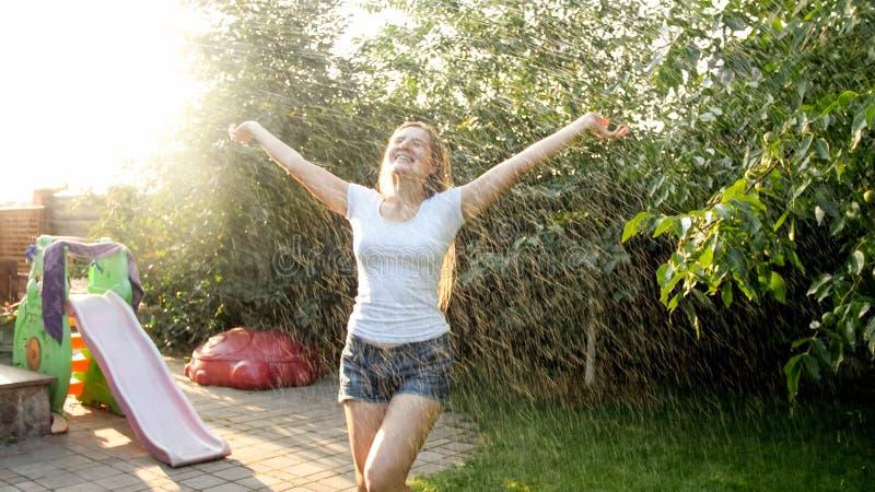 Portr?t der sch?nen l?chelnden Frau in der nass Kleidung warmen Regen am Haushinterhofgarten bei Sonnenuntergang genie?end Spiele stockfotografie