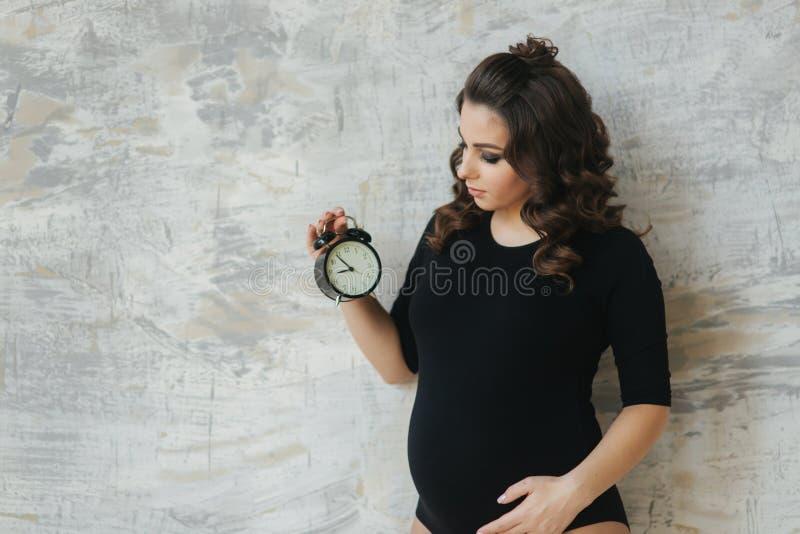 Portr?t der sch?nen schwangeren Frau im schwarzen Bodysuit Sie h?lt die Uhr in der Handsymbolischen Anspielung auf das Remanining lizenzfreies stockbild