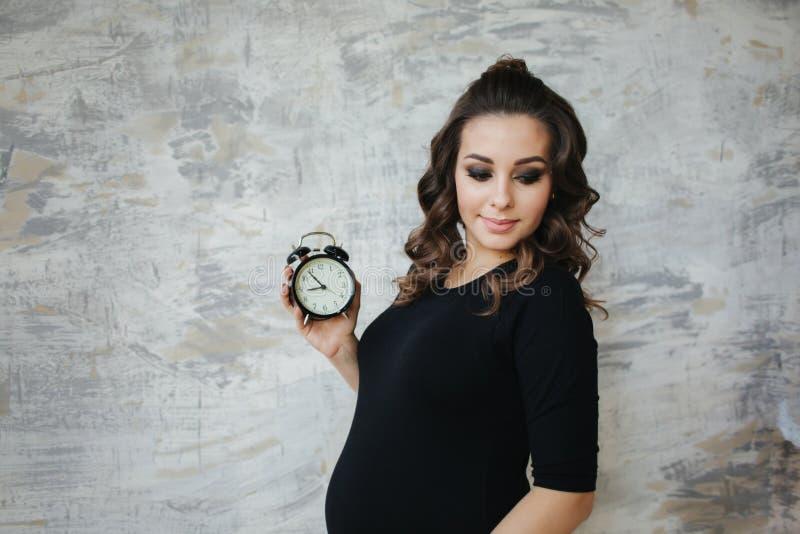 Portr?t der sch?nen schwangeren Frau im schwarzen Bodysuit Sie h?lt die Uhr in der Handsymbolischen Anspielung auf das Remanining lizenzfreie stockfotos