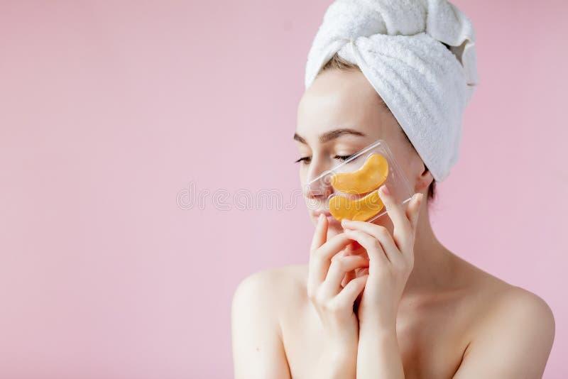 Portr?t der Sch?nheits-Frau mit Augenklappen auf rosa Hintergrund Frauen-Sch?nheits-Gesicht mit Maske unter Augen Sch?ne Frau mit lizenzfreies stockfoto