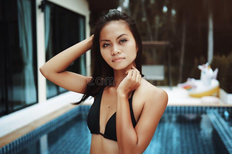 Portr?t der sexy asiatischen orientalischen Frau, die einen Bikini tr?gt und auf der Seite eines Swimmingpools sich entspannt stockfoto
