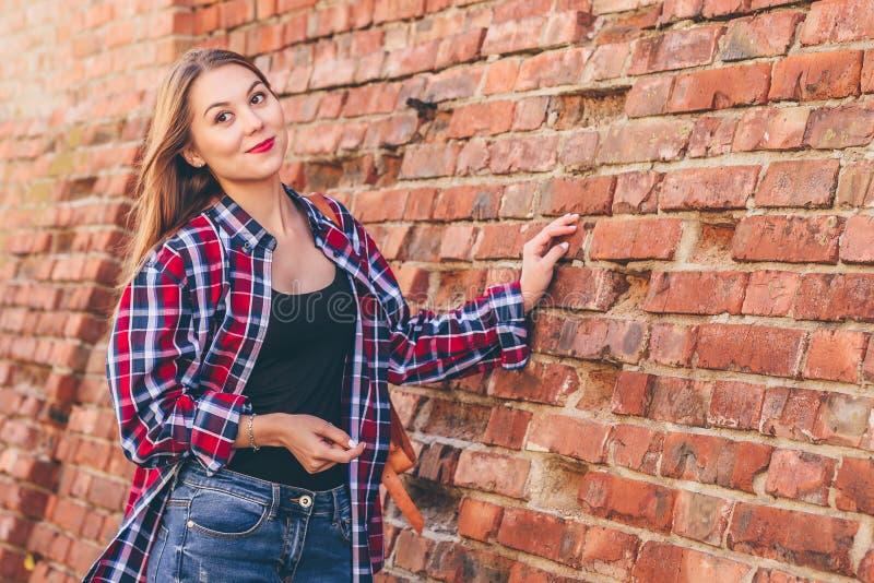 Portr?t der Stellung der jungen Frau gegen Backsteinmauer lizenzfreies stockfoto