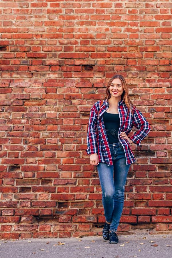 Portr?t der Stellung der jungen Frau gegen Backsteinmauer lizenzfreies stockbild