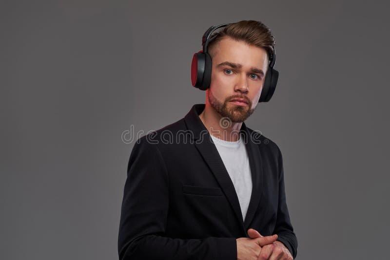 Portr?t des attraktiven jungen Mannes in den drahtlosen Kopfh?rern, der h?rende Musik ist stockfoto