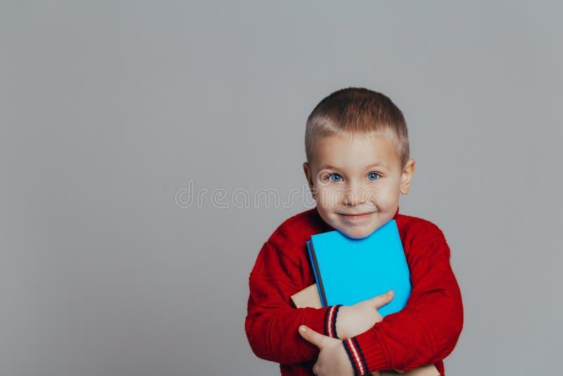 Portr?t des attraktiven l?chelnden Jungen in einer roten Strickjacke mit Buchnahaufnahme stockbilder
