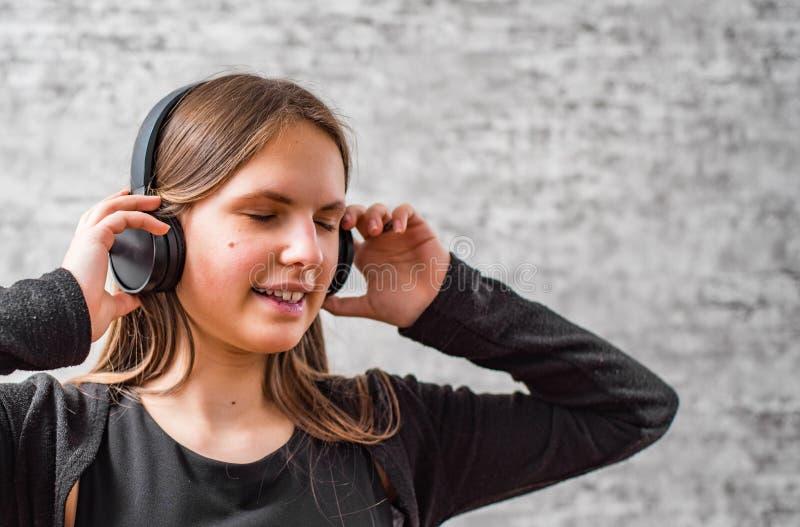 Portr?t des brunette M?dchens des jungen Jugendlichen mit h?render Musik des langen Haares auf drahtlosen Kopfh?rern stockfoto