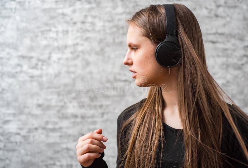Portr?t des brunette M?dchens des jungen Jugendlichen mit h?render Musik des langen Haares auf drahtlosen Kopfh?rern lizenzfreie stockfotos