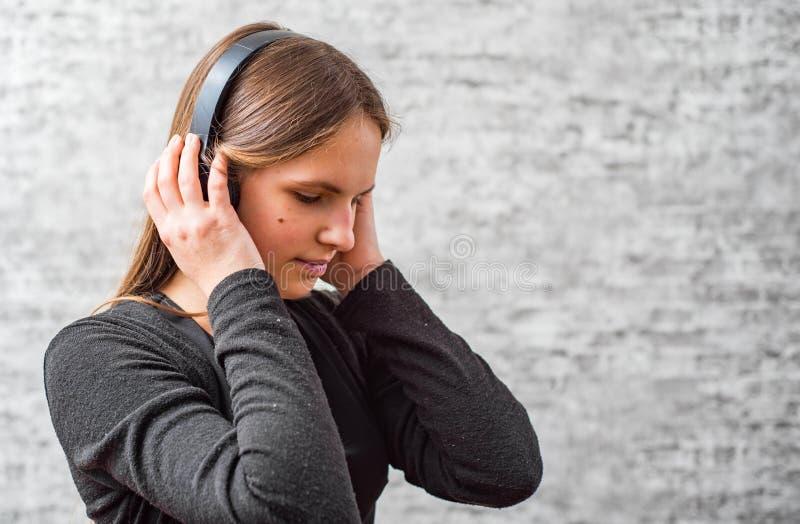 Portr?t des brunette M?dchens des jungen Jugendlichen mit h?render Musik des langen Haares auf drahtlosen Kopfh?rern lizenzfreie stockbilder