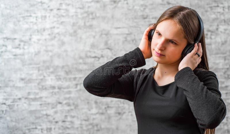Portr?t des brunette M?dchens des jungen Jugendlichen mit h?render Musik des langen Haares auf drahtlosen Kopfh?rern stockbilder