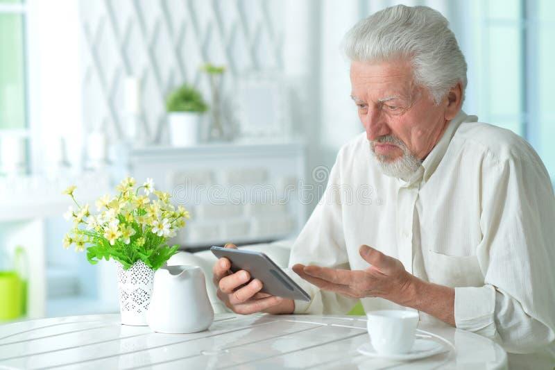 Portr?t des durchdachten ?lteren Mannes unter Verwendung der Tablette lizenzfreies stockfoto