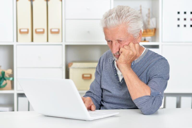 Portr?t des emotionalen ?lteren Mannes unter Verwendung des Laptops lizenzfreie stockfotos