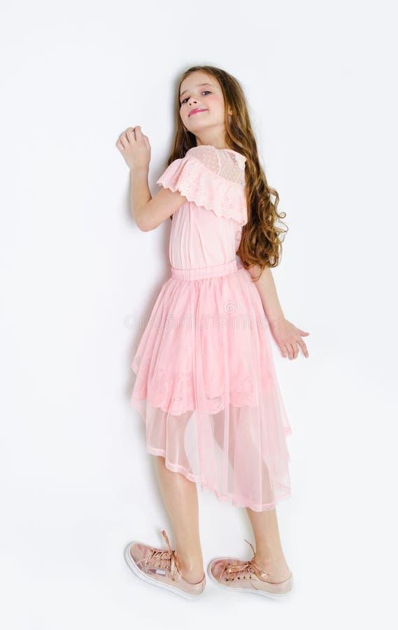 Portr?t des entz?ckenden l?chelnden Kindes des kleinen M?dchens in Prinzessinkleid mit dem Lockenhaar, das auf einem Boden lokali lizenzfreie stockfotografie