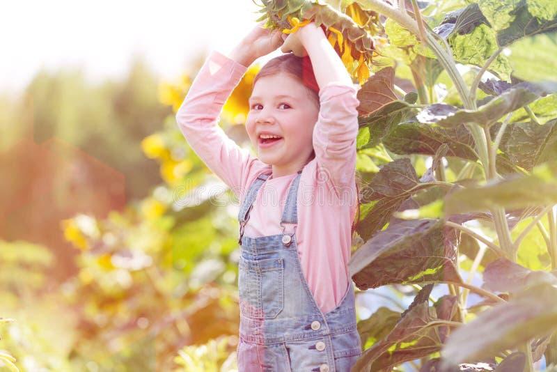 Portr?t des gl?cklichen M?dchens spielend mit Sonnenblume am Bauernhof stockfotos