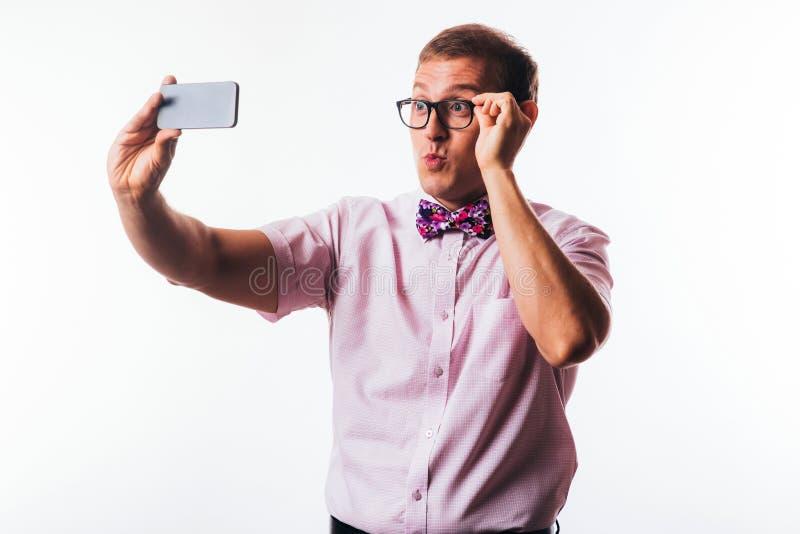 Portr?t des h?bschen jungen Mannes, Holding Smartphone, Kamera und das Lachen betrachtend lizenzfreie stockbilder