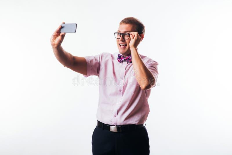 Portr?t des h?bschen jungen Mannes, Holding Smartphone, Kamera und das Lachen betrachtend stockfotografie