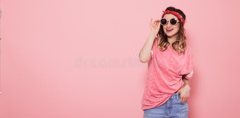 Portr?t des Hippie-M?dchens in den Gl?sern auf rosa Hintergrund lizenzfreie stockfotos