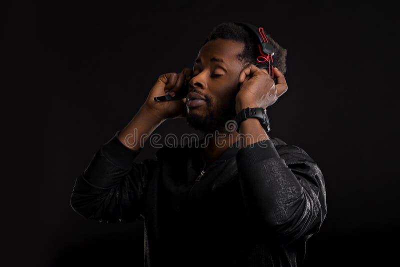 Portr?t des jungen afrikanischen Mannes, der Musik mit Kopfh?rern h?rt lizenzfreie stockfotos