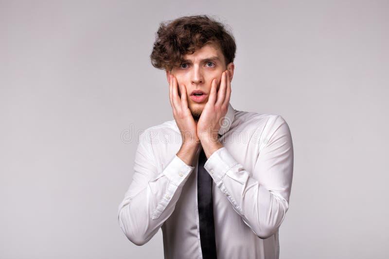 Portr?t des jungen Mannes mit entsetztem emotionalem Gesichtsausdruck und Handgeste ?ber hellgrauem Hintergrund stockfotografie