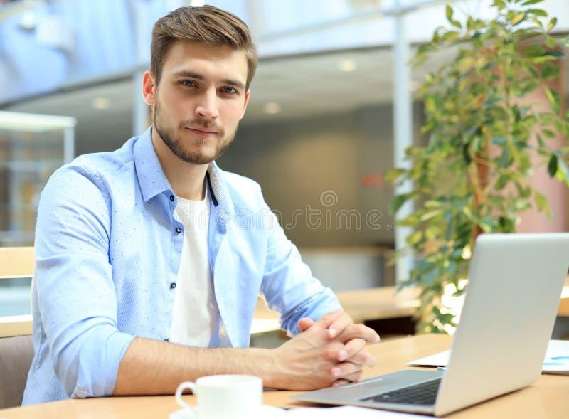 Portr?t des jungen Mannes sitzend an seinem Schreibtisch im B?ro lizenzfreie stockfotos