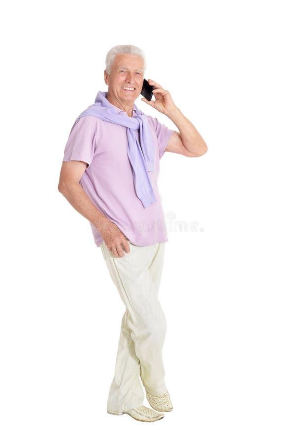 Portr?t des ?lteren Mannes sprechend am Telefon auf wei?em Hintergrund lizenzfreie stockfotos