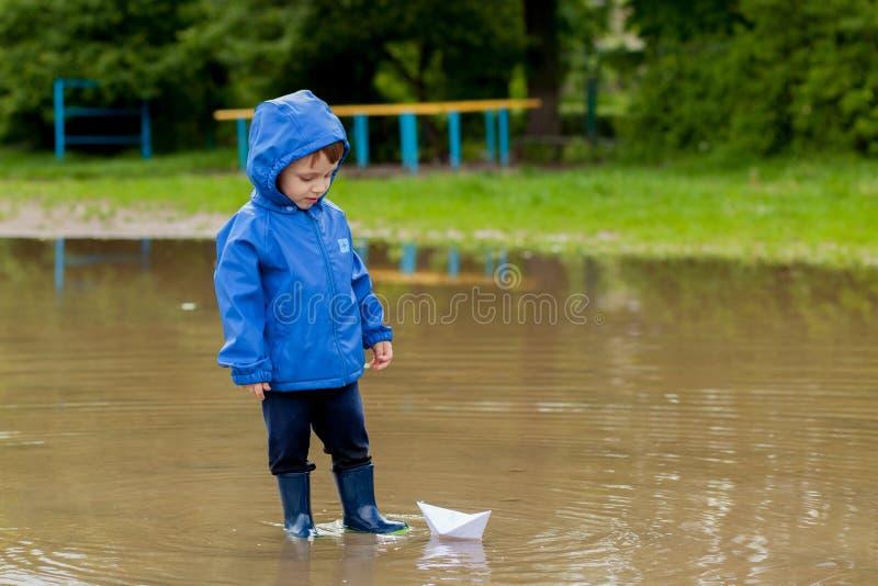 Portr?t des netten Kinderjungen, der mit handgemachtem Schiff spielt Kindergartenjunge, der ein Spielzeugboot durch den Rand des  lizenzfreies stockfoto