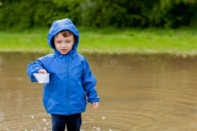 Portr?t des netten Kinderjungen, der mit handgemachtem Schiff spielt Kindergartenjunge, der ein Spielzeugboot durch den Rand des  stockbild
