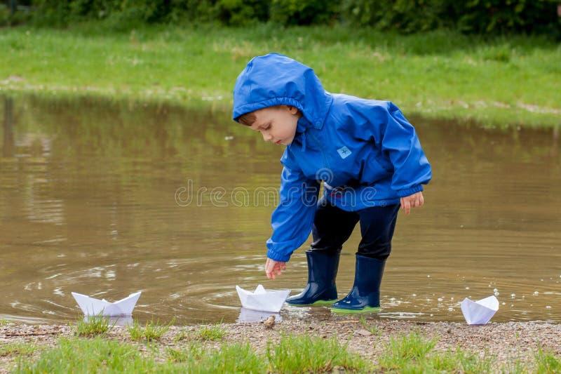 Portr?t des netten Kinderjungen, der mit handgemachtem Schiff spielt Kindergartenjunge, der ein Spielzeugboot durch den Rand des  stockfotografie