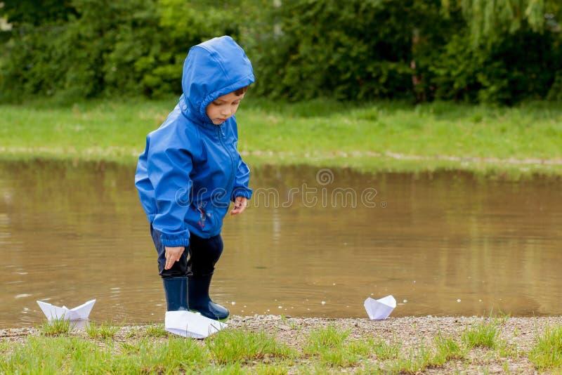 Portr?t des netten Kinderjungen, der mit handgemachtem Schiff spielt Kindergartenjunge, der ein Spielzeugboot durch den Rand des  lizenzfreie stockbilder