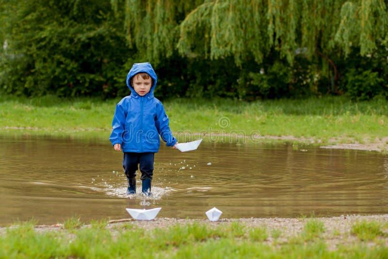 Portr?t des netten Kinderjungen, der mit handgemachtem Schiff spielt Kindergartenjunge, der ein Spielzeugboot durch den Rand des  lizenzfreies stockbild