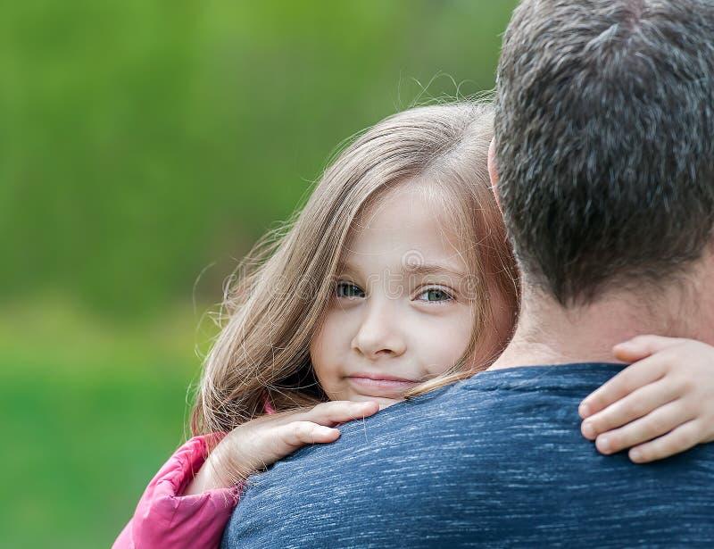 Portr?t des netten kleinen M?dchens hielt in Vater ` s Armen Gl?ckliche liebevolle Familie Bringen Sie und sein Tochterkinderm?dc stockbilder
