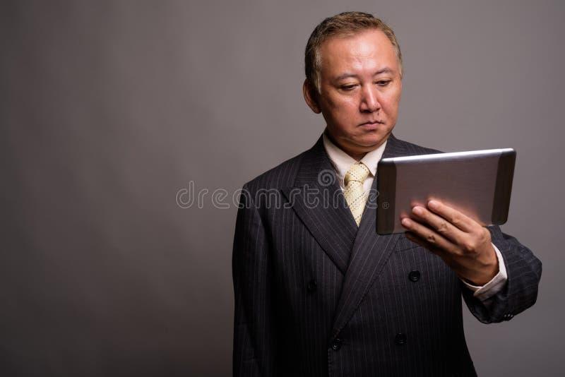 Portr?t des reifen asiatischen Gesch?ftsmannes gegen grauen Hintergrund stockbild