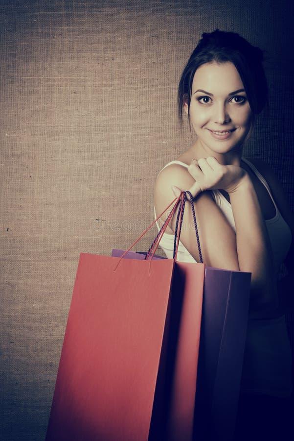 Portr?t des sch?nen M?dchens farbige Einkaufstaschen halten stockfotografie