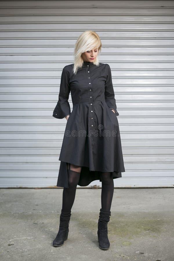 Portr?t des sch?nen modernen langen M?dchens des blonden Haares, das elegantes Kleid vor Stra?enhintergrund tr?gt stockfotos