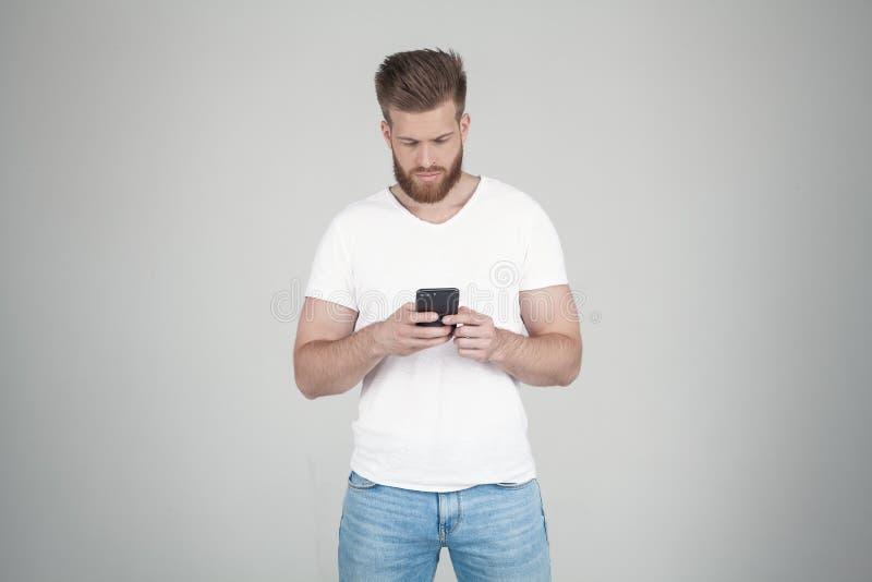 Portr?t des sch?nen sexy b?rtigen Mannes er schreibt seinen Freunden oder Freundin SMS er steht vor dem wei?en Hintergrund lizenzfreie stockbilder