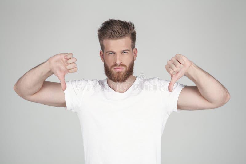 Portr?t des sch?nen sexy b?rtigen Mannes Zeigt zwei Finger unten er steht vor dem wei?en Hintergrund lizenzfreie stockbilder