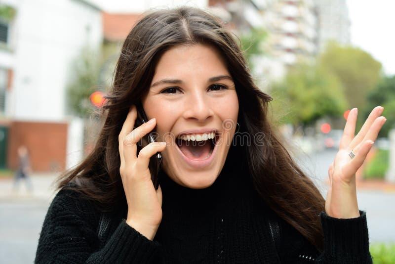 Portr?t einer ?berraschten Frau, die am intelligenten Telefon spricht lizenzfreies stockfoto
