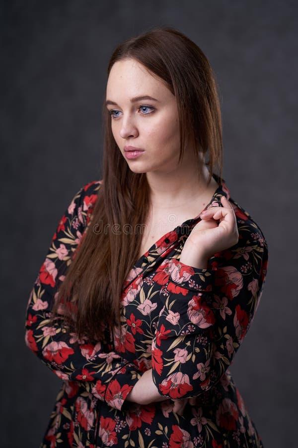 Portr?t einer Frau in einem farbigen Kleid auf grauem Hintergrund lizenzfreie stockbilder