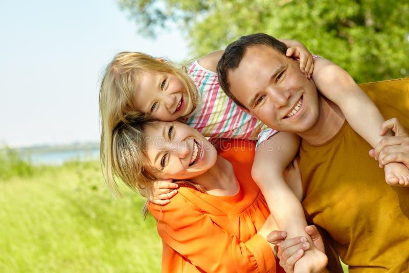 Portr?t einer gl?cklichen spielenden Familie drau?en Eltern mit Tochter im Sommer Mutter, Vati und Kind stockfoto