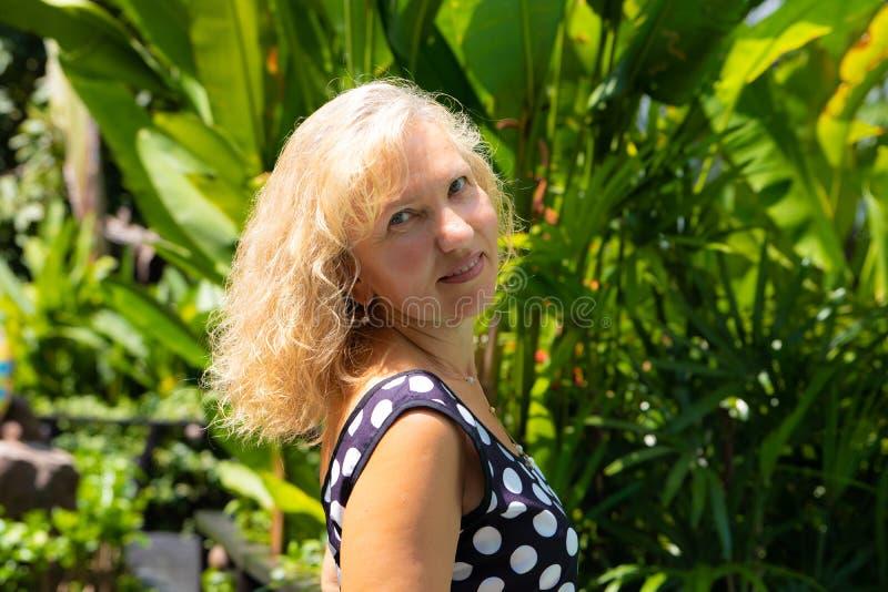 Portr?t einer 50-j?hrigen Frau im Sommer gegen einen Hintergrund von gr?nen tropischen Palmen lizenzfreies stockfoto